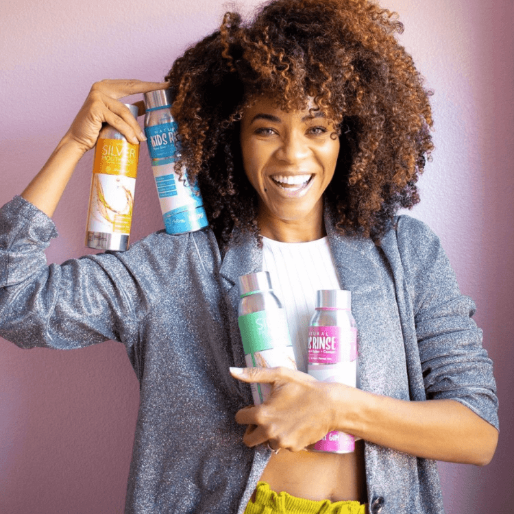 photo of female influencer holding differnt flavors of Elementa Silver mouth rinse