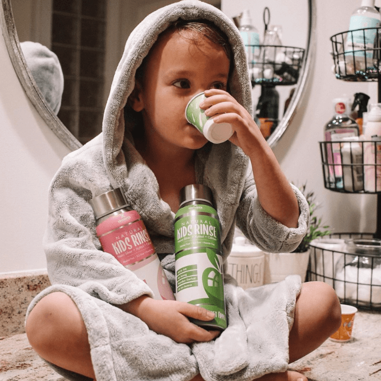 image of child in robe in bathroom using nano silver kids mouth rinse from Elementa Silver