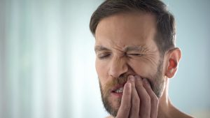 man wincing in pain because of sore gums