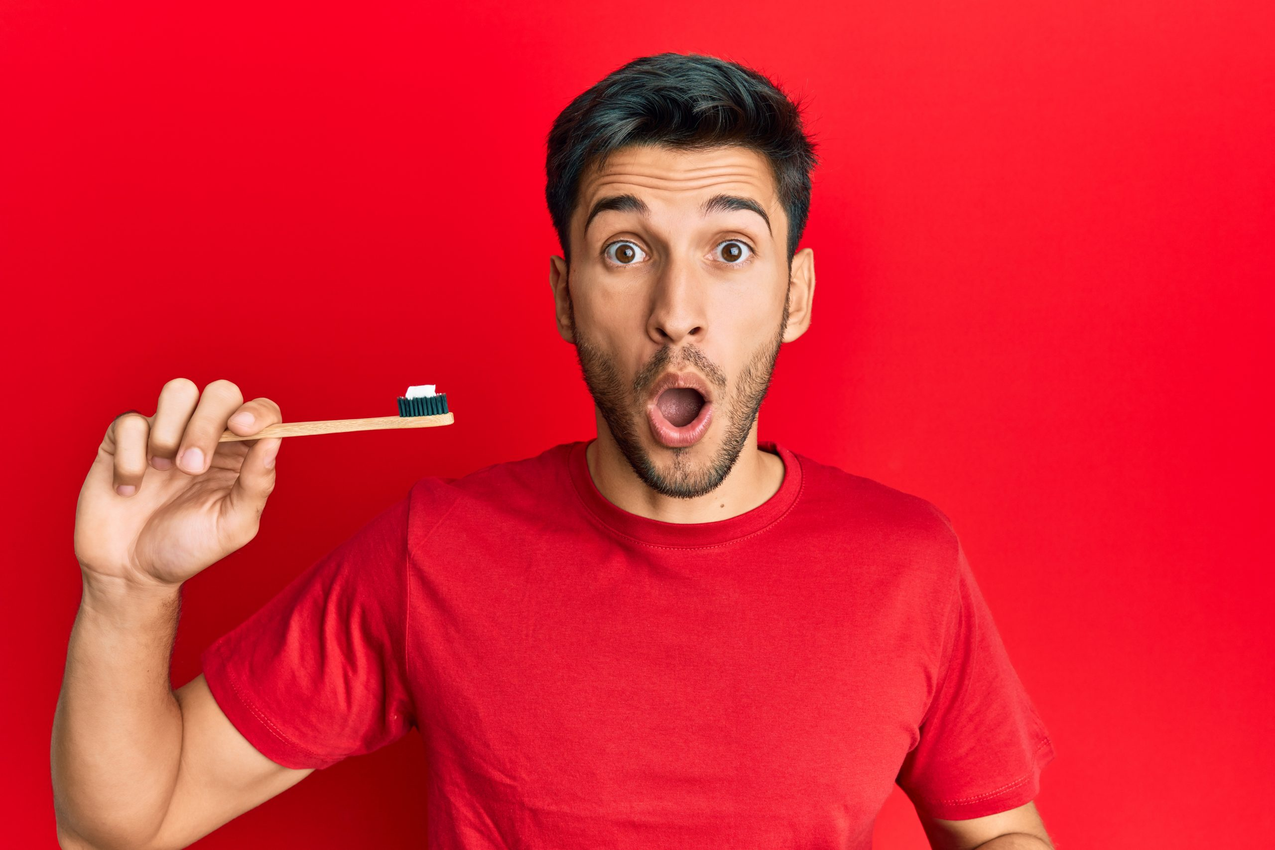 surprised man holding toothbrush about to brush teeth with non vegan toothpaste