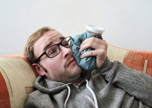 man with glasses using ice to recover from a root canal